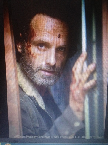 WD's first still shot for Season 5, Rick Grimes super tasty (in more ways than one, apparently) as he peers out of his train car storage unit.