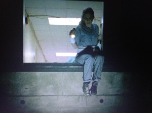 We see poor Beth, dressed in prison-looking scrubs, peering down a steep elevator shaft, looking for a way out of what looks like Hell.