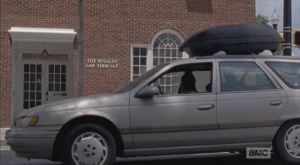 We see Carol pull up in front of a law office building that looks secure, windows intact.