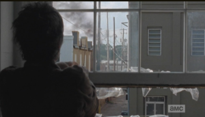 The next day, as Carol assembles a rain catcher out the window, she sees a black plume of smoke  in the horizon...it is coming from the direction of the prison.  After a moment's hesitation, Carol rushes out of  the office...