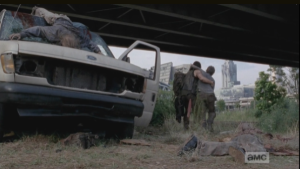 Daryl and Carol lean on each other as they help each other walk away from the totaled van and scattered walkers.