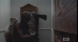 Wearing Baby Judith on her back, Michonne looks like the most badass momma ever, chopping at the boarded up church doors with an axe...babywearing, zombie-apocalypse style!