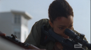 Sasha peers through the rifle scope, refocusing on the task at hand.