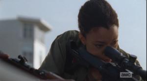Sasha peers through the rifle scope, refocusing on the task at hand.