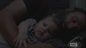 Maggie looks into Baby Judith's sweet face.  The baby is awake, but seems to know to let her dad sleep a little longer...Rick, once again, is looking like the hottest single dad ever, sleeping, holding his baby girl.