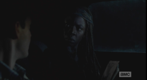 Michonne, alarmed, looks up, asks Aaron why he doesn't have any pictures of his people?