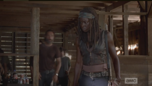 Michonne steps forward, in a role reversal with Rick, who hangs back, and interrupts Aaron.