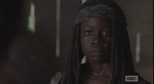 Michonne's face, and manner, become firm, no-nonsense.
