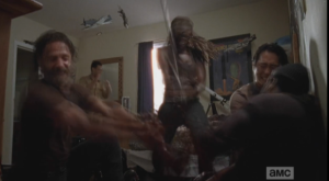 ...and the scene shifts quickly to Rick, Glenn, and Michonne, holding Tyreese while Michonne swiftly amputates poor Tyreese's bitten arm.
