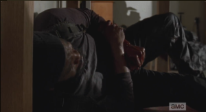 Tyreese is in agony now, struggling to get himself under a desk for some degree of cover.  He looks up at Second Act Walker, dead, body slumped over a desk chair.  The walker's blood is dripping...
