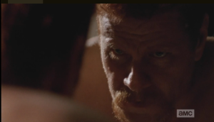 Abraham's face is grim as he peers at his reflection in the mirror.