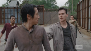 Aidan charges up behind Glenn, reaches out and stops him,