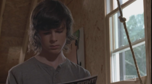 Carl picks up a comic and starts reading.