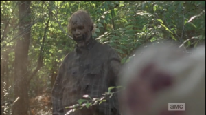 Carol keeps firing bullets into the walker's chest, and finally drops it with a shot to the head.  At Rick's questioning look, Carol explains that they said they were going shooting, and she couldn't very well come back with a full mag...