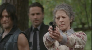 Carol, however, motions to the men...she's got this.  She points her gun and starts shooting at the approaching walker.
