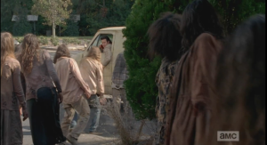 Eugene leads the walkers outside away from the doors.