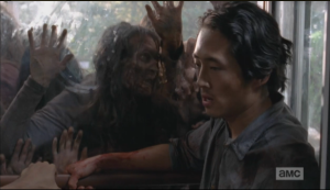 Glenn tries to think of a way as the walkers paw and push,  trying to get at them.