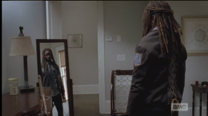 Meanwhile, Michonne models her new constable's uniform in the mirror.