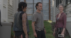 As Carol grins benignly at a curious passerby, Rick and Daryl try to look casual...just a neighborly yard chat, here.  Looking away, Rick informs them that they will all be sleeping in the same house tonight.