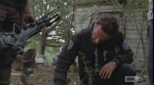 Rick kneels over the walker, studies it a long moment...surely he must remember those walker heads and upper torsos that fell on the van's hood back at the Shirewilt Estates, 100 miles away...those walkers' foreheads, too, were clearly marked with