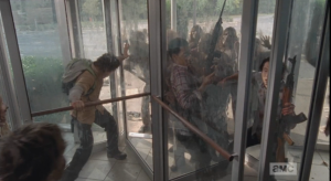 In the center sections, Nicholas braces himself, alone, in one enclosed middle section, while Noah and Glenn are together in the opposite enclosed middle section, with swarms of walkers on both sides, outside and in.