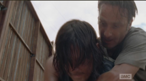 Before Daryl can unleash some pent-up frustration on Nicholas, Rick grabs him from behind,
