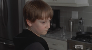 As Carol does her best to try to be mean and run the young boy off, Sam just looks off sadly in the kitchen.  It seems like he is used to people being mean around him.