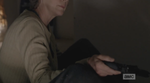 Carol holds out another handgun to Rick, and after a moment, he takes it.