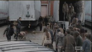 There are too many walkers to fight through, and Aaron and Daryl dive under one of the tractor trailers for momentary cover.