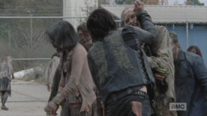 Daryl and Aaron must fight through the first wave of walkers...Daryl uses his knife to spear through the walkers' rotten skulls...