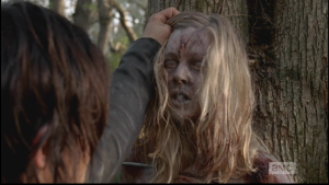 As Daryl holds the young woman's head up, her eyes flutter open as she reanimates.