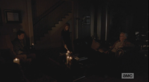 Deanna comes back into her living room with Carol's sympathy note, and holds the note to the candle's flame.
