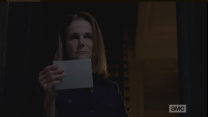 Deanna reaches down, picks up the note and reads its message, then looks up from the note, her expression still grim.