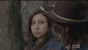 Enid looks at Carl, says nothing. She seems to want to tell him, but then, the telltale snarl of walkers approaching interrupt their sweet moment.