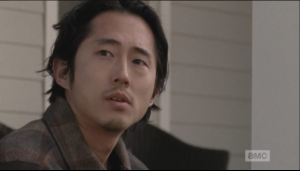 After Maggie leaves, Glenn sits a moment more on the porch, thinking...a sudden noise makes him look up, and he sees...