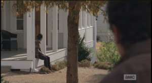Glenn sits on the porch, waiting for Maggie to return from her meeting with Deanna as a shady lurker watches him from the shadows....
