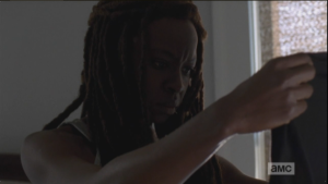 Michonne gets out of bed, walks over, and picks up Noah's shirt, looks at it a long moment.