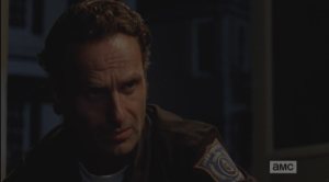 Glenn looks miserably up at Rick, who is sitting with him, watching him, listening.