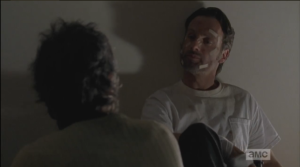After taking the gun, Rick looks at Carol.