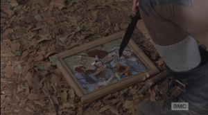Rosita then kneels down, touches the shattered picture that Sasha had used as target practice a day or two earlier with the tip of her knife.