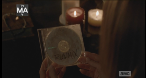 ...in the home of the Monroes, there seems to be a vigil being held for Aiden. Candles are lit, and we see Deanna's hands holding a cd of another one of Aiden's specialty
