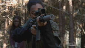 Sasha lifts her rifle and peers through the scope as Michonne looks on dubiously...