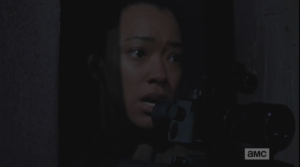 ...but as Sasha tries to peer through the scope, and focus, we see she is shaking, distressed, near tears.