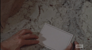 Carol pauses above the blank notecard...