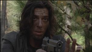 The young man motions Morgan back, while pointing the gun at Morgan.