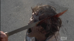 Aaron brings his machete down on a walker's head...
