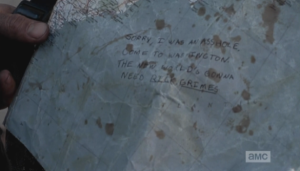 ...who takes the map Morgan has handed him, and looks down to see Abraham's note to Rick: