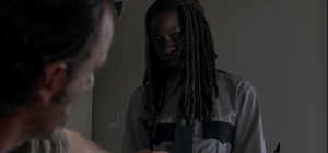 Michonne tosses the constable's jacket on the bed, fixes Rick with a look.