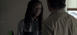 Michonne's face softens as she looks at the big adorable dummy in front of her.