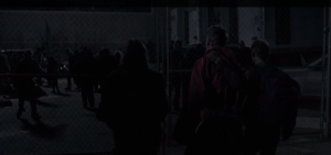 We see the Wolfboys walking Red Poncho Guy, whose hands are tied behind his back, up to the gates of the distribution center, where the walkers snarl and grab at the fence.